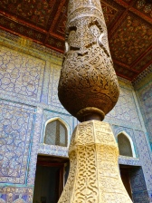 ::intricate wood and marble carvings on the ayvan columns::